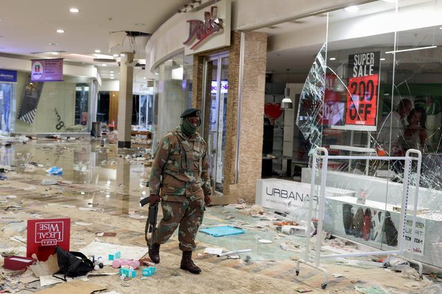 A member of the military walks as he inspects the damage at the looted Jabulani mall as the country deploys army to quell unrest linked to jailing of former President Jacob Zuma, in Soweto, South Africa, July 13, 2021. (Photo by Siphiwe Sibeko/Reuters)