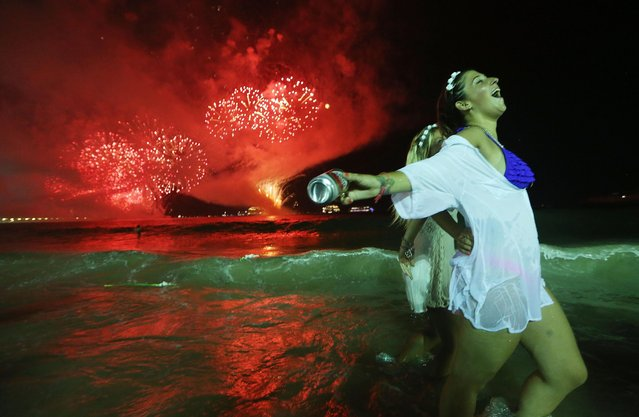Revelers celebrate during fireworks marking the start of the New Year on Copacabana beach on January 1, 2017 in Rio de Janeiro, Brazil. Brazilian revelers traditionally dress in white to honor the New Year's holiday along with the Brazilian Goddess of the Sea- Iemanja. (Photo by Mario Tama/Getty Images)