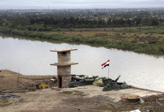 An Iraqi flag waves over the Tigris River at a checkpoint in Tikrit, 80 miles (130 kilometers) north of Baghdad, Iraq, Wednesday, April 1, 2015. (Photo by Khalid Mohammed/AP Photo)