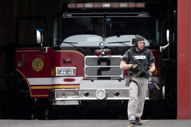 An officer walks out of the LaMott Fire Company after police escorted a man away, Tuesday, March 31, 2015, in Elkins Park, Pa. Authorities say a former volunteer firefighter held four firefighters hostage at the Philadelphia-area firehouse before surrendering to police. No injuries were reported. (Photo by Matt Rourke/AP Photo)