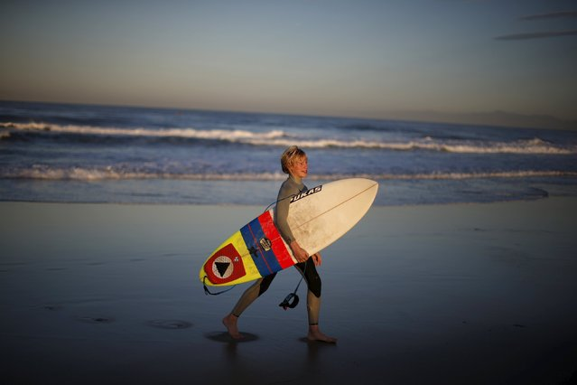 Carlos Price Gracida, 13, walks out of the water after surfing at sunrise in Hermosa Beach, California March 24, 2015. (Photo by Lucy Nicholson/Reuters)