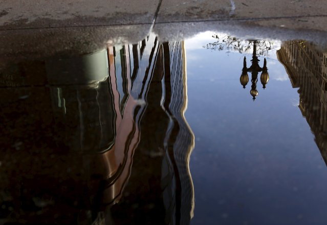 A building is reflected in a rain puddle on Market Street in San Francisco California April 7, 2015. (Photo by Robert Galbraith/Reuters)