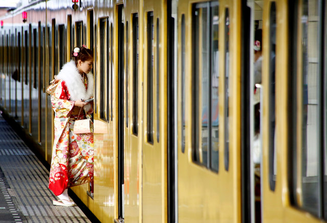A Japanese woman wearing a kimono gets on a train after the Coming of Age Day celebration in Tokyo, Japan January 9, 2017. (Photo by Kim Kyung-Hoon/Reuters)