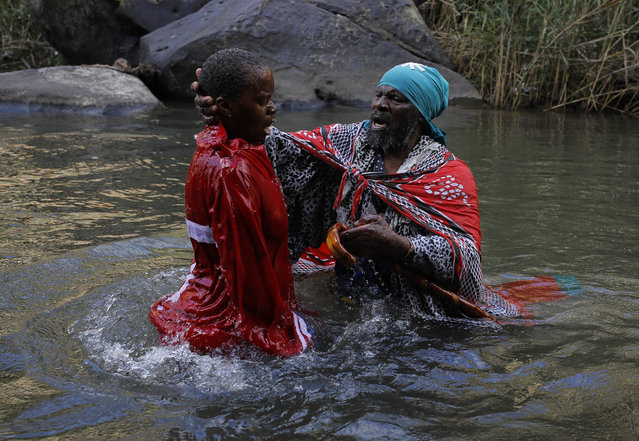 A priest from the national Catholic Church of Zion holds a pilgrim as he cleanses her in the waters of the Caledon River during the pilgrimage to the Fertility Cave near Clarens, South Africa, April 5, 2015. The pilgrims intend to evoke their African ancestors while asking them to connect them with their Christina God. The cave is a popular pilgrimage for spiritual seekers and sees the combination of worship to African ancestors as well as connection to the Christian God. (Photo by Kim Ludbrook/EPA)