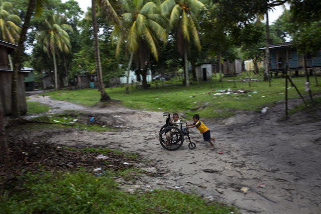 In this February 6, 2018 photo, Charles Melendez, 5, and his 4-year-old brother Jefferson, play with their father's wheelchair while he rests, in Puerto Lempira, Honduras. The boys' father, a lobster diver, is recovering from decompression sickness which has left him paralyzed from the waist down. (Photo by Rodrigo Abd/AP Photo)
