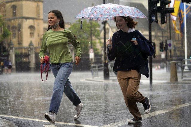 Two women run through Parliament Square in central London, Sunday July 25, 2021. Thunderstorms bringing lightning and torrential rain to the south are set to continue until Monday it is forecast. (Photo by Victoria Jones/PA Wire via AP Photo)
