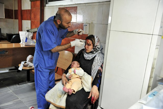 A wounded woman carries a baby as she receives treatment inside a hospital after multiple bomb blasts hit a southern district of Damascus, Syria, in this handout picture provided by SANA on February 21, 2016. (Photo by Reuters/SANA)