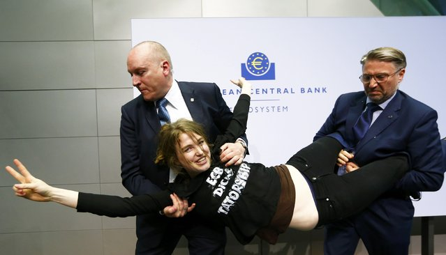 Security officers carry away a protester who jumped on the table in front of the European Central Bank President Mario Draghi during a news conference in Frankfurt, April 15, 2015. (Photo by Ralph Orlowski/Reuters)