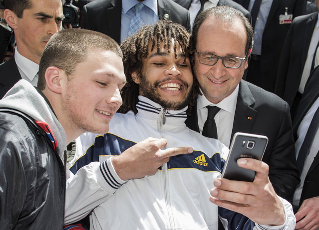 "Two men take a selfie with French President Francois Hollande, right, at the ""Muensterplatz"" square in Bern, Switzerland, Wednesday, April 15, 2015. Hollande is on a two-day official visit in Switzerland. (Photo by Thomas Hodel/Keystone via AP)"