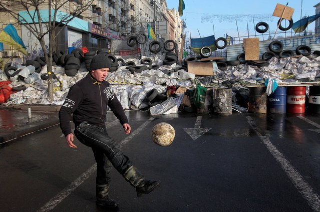 A Pro-European Union activist plays with the ball in front of barricades at the Independence Square in Kiev, Ukraine, Sunday, December 29, 2013. About 20,000 people protested in Ukraine's capital on Sunday, maintaining more than a month of rallies opposing the government's decision to shelve a key deal with the European Union. (Photo by Sergei Chuzavkov/AP Photo)