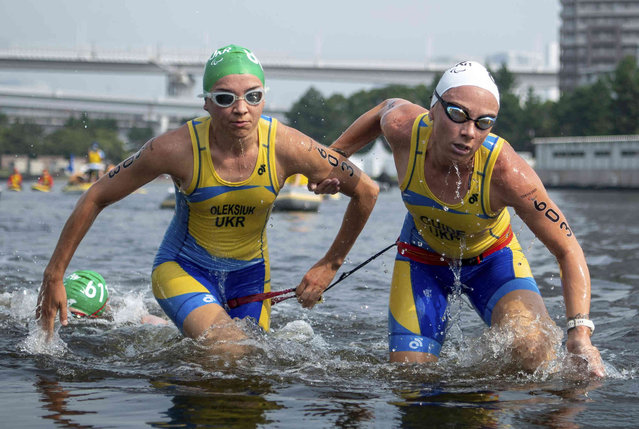 Ukraine's Vita Oleksiuk, left, and her guide exit the water at the end of the swimming stage in the women's triathlon PTV1 at Odaiba Marine Park during the Tokyo 2020 Paralympic Games on Saturday, August 28, 2021, in Tokyo. (Photo by Joel Marklund for OIS via AP Photo)
