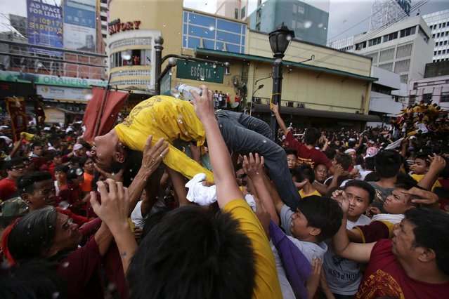 A Filipino Catholic devotee is carried to safer grounds as she collapses while joining  an annual procession of the Black Nazarene to celebrate its feast day Thursday January 9, 2014 in Manila, Philippines. (Photo by Aaron Favila/AP Photo)