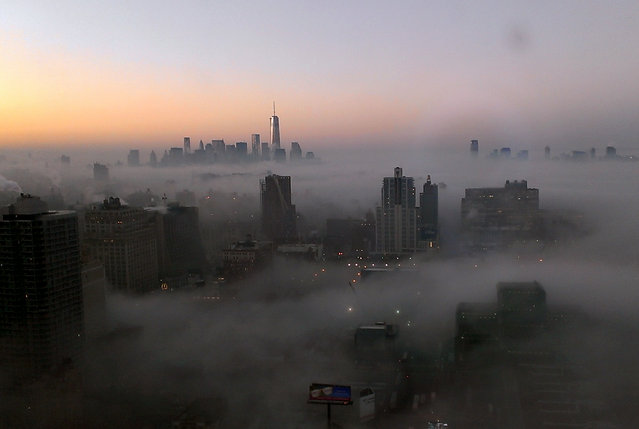 The tower of New York's World Trade Center rises through a blanket of fog on Wednesday morning, Jan. 15, 2014, in this view looking south from the 48th floor at 42nd St. and 11th Ave in Midtown Manhattan. New Jersey is visible at top right. (Photo by Girish Tewani/AP Photo)