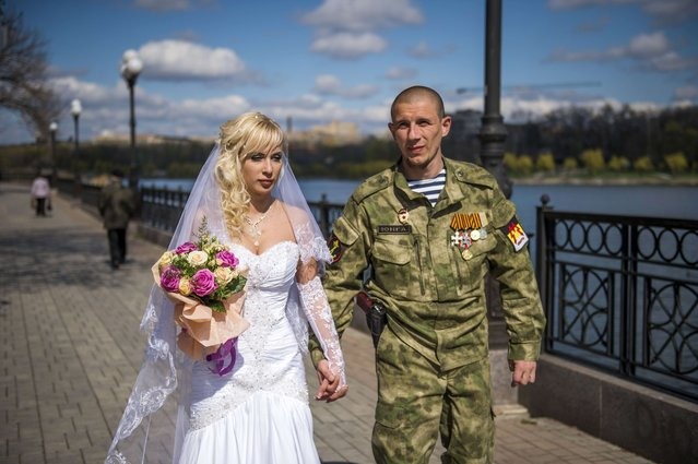 Pro-Russian separatist Junga (war name) and his bride walk along river Kalmius after getting married in Donetsk on April 22, 2015 in the self-proclaimed Donetsk People's Republic (DNR). (Photo by Odd Andersen/AFP Photo)