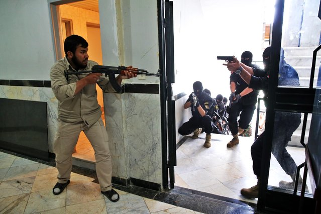 A group of Iranian paramilitary Basij forces, affiliated to the Revolutionary Guard, re-enact an operation to release hostages during training in a Guard base in northeastern Tehran, Iran, Friday, April 24, 2015. The volunteer Basij force is often used to quell civil unrest and oversea civilian behavior. (Photo by Ebrahim Noroozi/AP Photo)