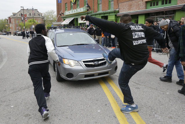 Protestors chase after a car as it drives in reverse after a rally for Freddie Gray, Saturday, April 25, 2015, in Baltimore. (Photo by Patrick Semansky/AP Photo)