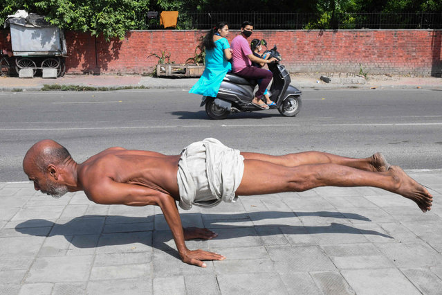 A man practices yoga along a footpath in Amritsar on October 6, 2021. (Photo by Narinder Nanu/AFP Photo)