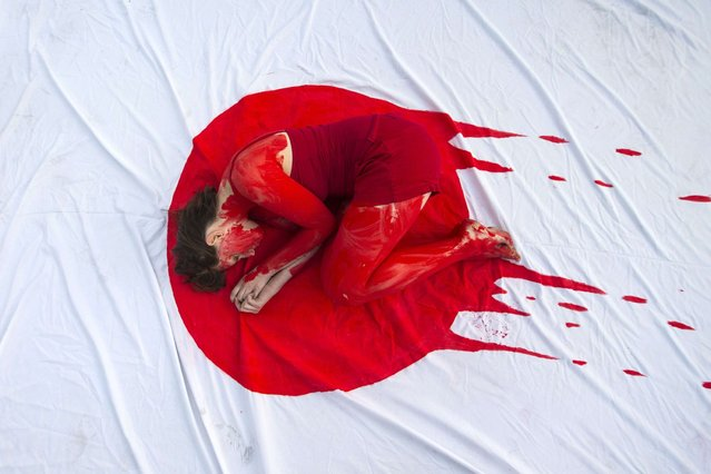 "An Israeli member of the ""Taiji Dolphin Action Group"", with a red body painting to evok blood, is curled up on a sheet depicting the Japanese flag, during a protest against the killing of dolphins, notably in the Japanese city of Taiji on January 30, 2014 outside the building housing the Japanese Embassy, in the Mediterranean coastal city of Tel Aviv. (Photo by Jack Guez/AFP Photo)"