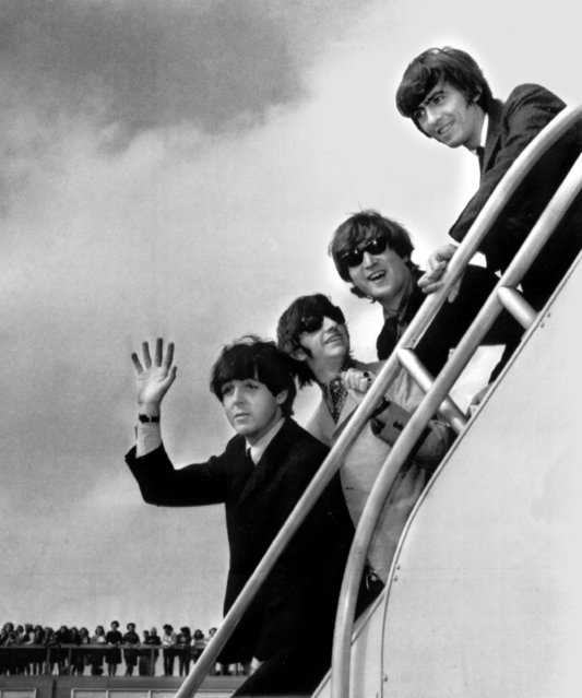 In this September 21, 1964, file photo The Beatles, from left, Paul McCartney, Ringo Starr, John Lennon and George Harrison board a plane for England at a New York airport with some of their fans in the background.  A new poll by the Pew Research Center examining the generation gap four decades after Woodstock and the rebel yell of 1960s youth finds that rock and roll rules across generations and the Beatles are high on the list of every age group's favorite bands. (Photo by AP Photo, File)