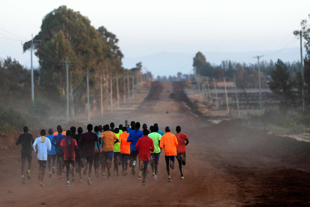 """A group of runners takes part a training sesion on March 13, 2019 in Iten, Kenya. From dawn until sunset, between Kapsabet, Iten and Kaptagat, the three """"spots"""" of the bottom in the Rift region, Kenyans dedicate their sports life in training centers, with the hope to become a prophet in the land of the king marathon. There are dozens of training centers in this area of the Kenyan highlands, which have provided the greatest riders in recent decades. (Photo by Franck Fife/AFP Photo)"""