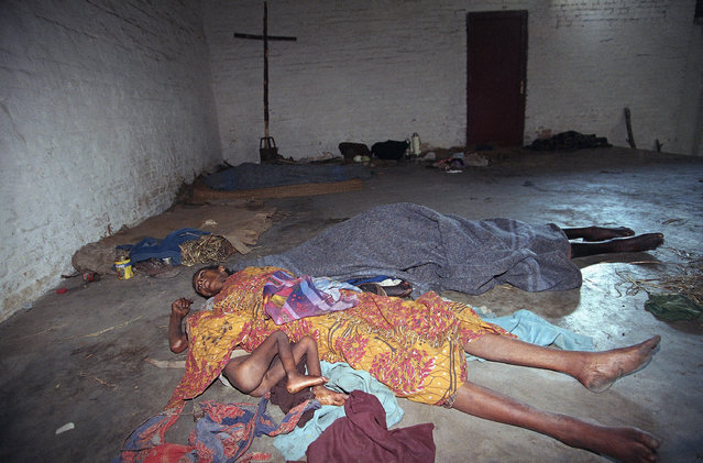 In this June 8, 1994, file photo, a little girl clutches the body of her mother, who died two days earlier of starvation, in the chapel of a seminary housing displaced Tutsis in Kabgayi. Rebels with the Rwandan Patriotic Front (RPF) found them six days after they took Kabgayi from government forces, who survivors said ran the compound as a concentration camp. (Photo by Jean-Marc Bouju/AP Photo/File)