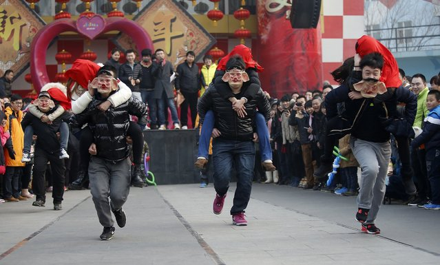 Men wearing pig masks carry their girlfriends on their backs as they run to be selected as finalists during a kissing contest held in celebration of Valentine's Day at the Happy Valley amusement park in Beijing February 14, 2014. About 100 couples competed by kissing in various poses during the competition and an iPhone 5S was presented to the winning couple. (Photo by Kim Kyung-Hoon/Reuters)