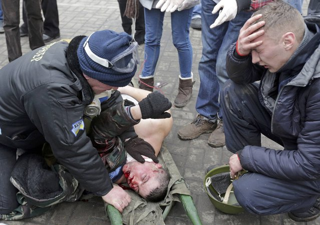 A wounded protester is attended before being rushed to a vehicle following violence in Independence Square in Kiev February 20, 2014. Ukrainian protesters seized back Kiev's Independence Square in fresh clashes with riot police on Thursday that left several injured and possibly two demonstrators dead. (Photo by Konstantin Chernichkin/Reuters)