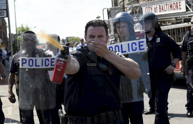 A law enforcement officer uses pepper spray to disperse the crowd at the intersection of North and Pennsylvania Avenues in Baltimore, May 4, 2015. (Photo by Sait Serkan Gurbuz/Reuters)