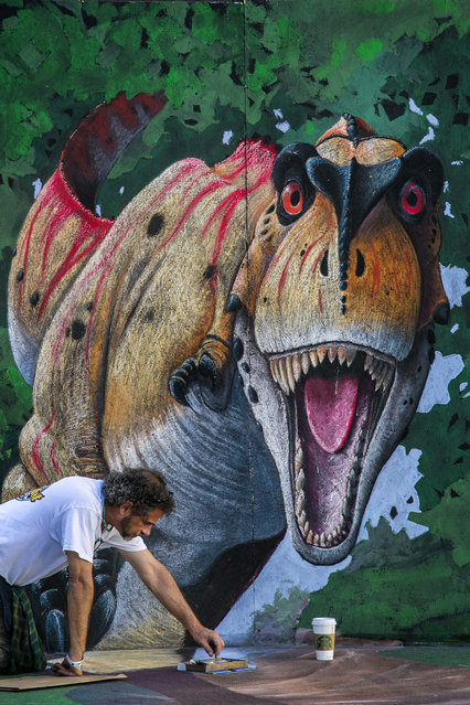 Mike Las Casas, of Palm Beach Gardens, paints the foot of a dinasour. (Photo by Greg Lovett/The Palm Beach Post)