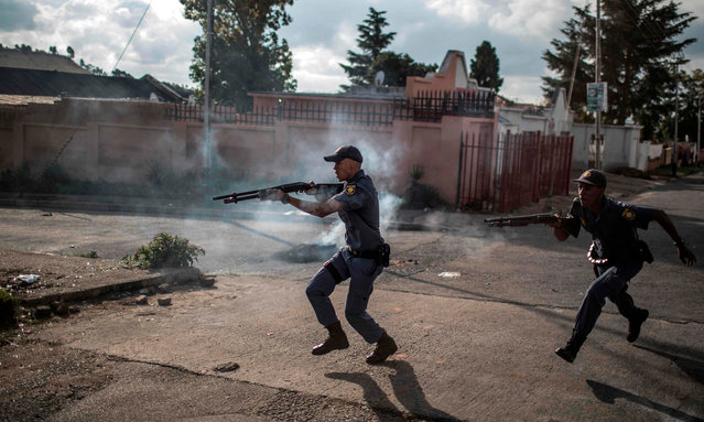 South African police officers fire rubber bullet as they chase protestors in the streets of Johannesburg, on April 23, 2019 during a protest against the lack of service delivery or basic necessities such as access to water and electricity, housing difficulties and lack of public road maintenance. - Police and protesters exchanged volleys of teargas and stones in Johannesburg on April 23, 2019 after a suburb erupted into protest over public services ahead of polls on May 8. Dozens of residents in the working class Turffontein suburb blocked the main road through ward 55, burning tyres, mattresses and tree branches over allegedly unfair allocation of nearby new social housing. (Photo by Marco Longari/AFP Photo)