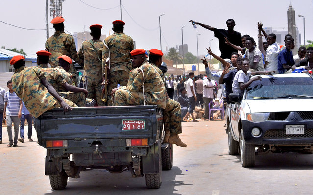 """Sudanese demonstrators cheer as they drive towards a military vehicle, after Sudan's Defense Minister Awad Mohamed Ahmed Ibn Auf said that President Omar al-Bashir had been detained """"in a safe place"""" and that a military council would run the country for a two-year transitional period, near Defence Ministry in Khartoum, Sudan April 11, 2019. (Photo by Reuters/Stringer)"""