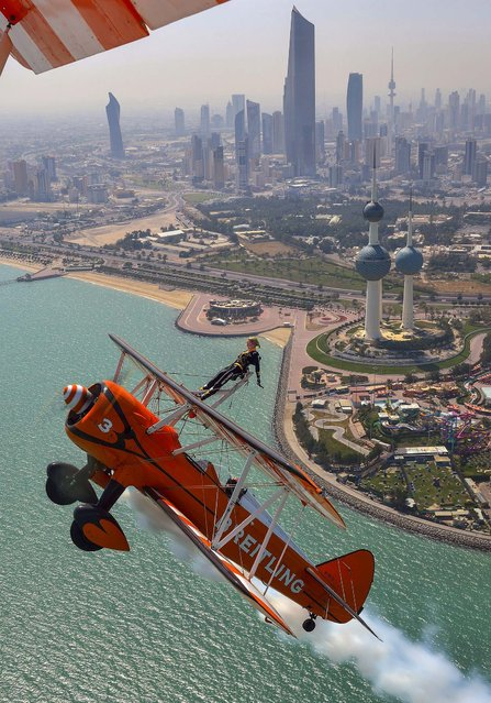 Breitling Wingwalker Freya Paterson, from Liverpool, UK, flies above Kuwait City's iconic Water Towers with pilots David Barrell and Martyn Carrington, on March 6, 2014. The team loop and roll up to 160 mph enduring G-forces of 4-5g. (Photo by Katsuhiko Tokunaga/Breitling)