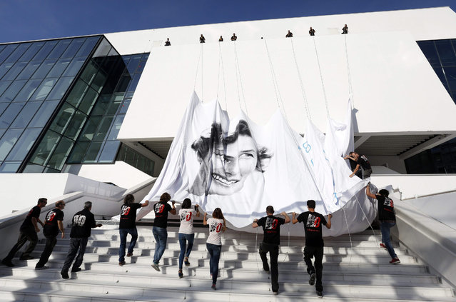 Workers set up the official poster of the 68th annual Cannes Film Festival on the Palais des Festivals facade, in Cannes, France, 11 May 2015. The poster displays a photograph of Swedish actress Ingrid Bergman taken by Polish photographer David Seymour. The film festival will run from 13 to 24 May. (Photo by Guillaume Horcajuelo/EPA)