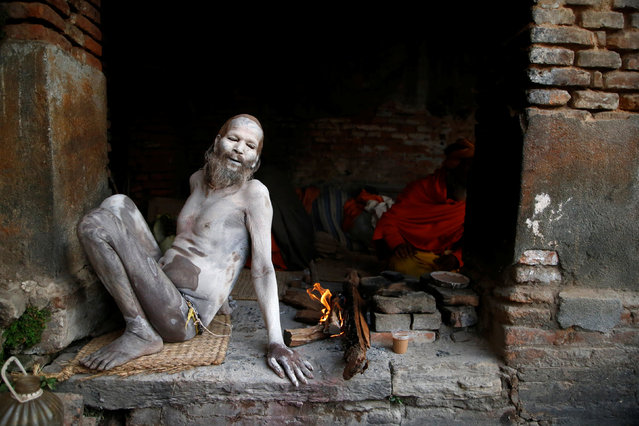 A Hindu holy man, or sadhu, sits beside a fire after smearing his body with ashes at the premises of Pashupatinath Temple, ahead of the Shivaratri festival in Kathmandu, Nepal February 21, 2017. (Photo by Navesh Chitrakar/Reuters)