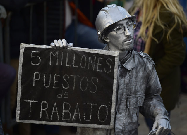 "A man doused in silver body paint holds a sign with a message that reads in Spanish: ""Five thousand jobs"", in reference to the informal job market, attends the kick-off campaign rally of presidential candidate Alberto Fernandez and his running mate, former President Cristina Fernandez, in Buenos Aires, Argentina, Saturday, May 25, 2019. (Photo by Gustavo Garello/AP Photo)"