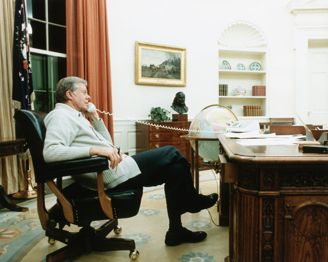 """President Jimmy Carter speaks on the phone in the Oval Office in Washington, DC. James Earl """"Jimmy"""" Carter, Jr. was the 39th U.S. President serving from 1977 – 1981. (Photo by Corbis)"""