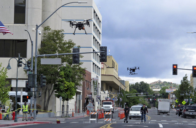In this Tuesday, May 21, 2019 photo, two drones fly above Lake Street in downtown Reno, Nev., on, as part of a NASA simulation to test emerging technology that someday will be used to manage travel of hundreds of thousands of commercial, unmanned aerial vehicles (UAVs) delivering packages. It marked the first time such tests have been conducted in an urban setting. (Photo by Scott Sonner/AP Photo)