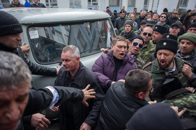 Crimean self-defense forces brawl with Ukrainian servicemen outside the Ukrainian navy headquarters in Sevastopol, Crimea, Wednesday, March 19, 2014. Crimea's self-defense forces on Wednesday stormed the Ukrainian navy headquarters in the Black Sea port of Sevastopol, taking possession without resistance a day after Russia signed a treaty with local authorities to annex the region. (Photo by Andrew Lubimov/AP Photo)