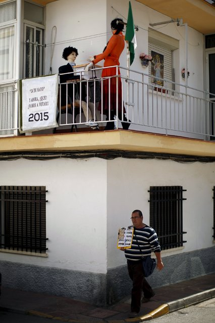 """A lottery ticket seller walks past an installation with mannequins by Jose Maria Leon, 73, (not pictured), depicting a woman (R) casting her vote in a polling station, on the balcony of Leon's flat in Ronda, southern Spain, May 23, 2015. The sign reads, """"May 24. And now, what? Let's vote!"""". (Photo by Jon Nazca/Reuters)"""