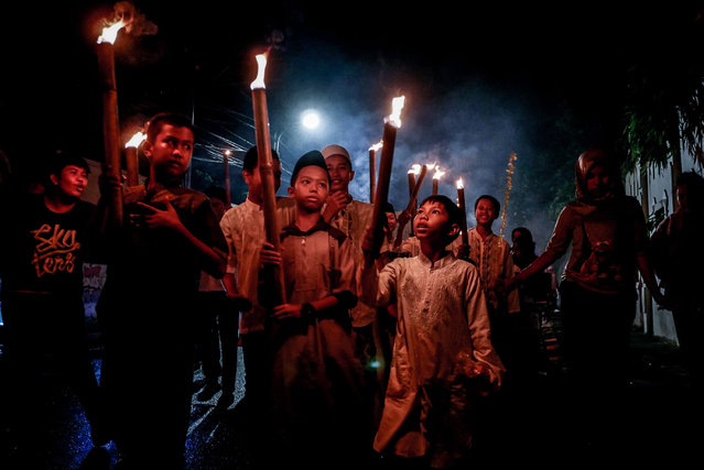 Children carry torches during a parade to welcome Muslim holy month of Ramadan in Jakarta, Indonesia on May 4, 2019. Ramadan is a fasting holy month for Muslims around the world where they refrain from eating, drinking, and all lust from dawn to dusk. (Photo by Anton Raharjo/Anadolu Agency/Getty Images)