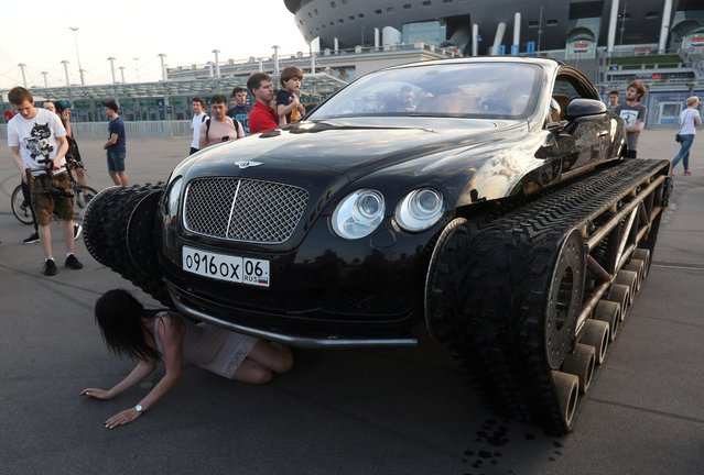 A woman poses for a picture next to a caterpillar-tracked Bentley Continental GT, which was modified by Russian car engineering enthusiasts, during a demonstration in St. Petersburg, Russia on June 7, 2019. (Photo by Anton Vaganov/Reuters)