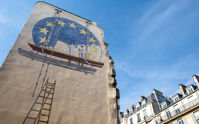 A trompe l'oeil shows two workers painting the European Union flag on the side of a building in the French capital Paris on May 23, 2019. Europe kicked off voting across the continent in a contest in which rising populist forces are hoping to make significant gains, threatening closer EU integration. (Photo by Joel Saget/AFP Photo)