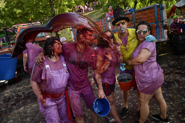 Revelers are covered in wine as people take part in a wine battle, in the small village of Haro, northern Spain, Saturday, June 29, 2019. Hundreds of revelers participate in this famous summer battle throwing thousands of liters of red wine over each other. (Photo by Alvaro Barrientos/AP Photo)