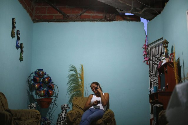 """Thais Ruiz (36) talks on the telephone and drinks coffee as she sits under a crack in the roof of her living room on the 27th floor of the """"Tower of David"""" skyscraper in Caracas. (Photo by Jorge Silva/Reuters)"""