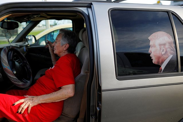 Dawn Simmons, a volunteer who organises Trump sign waving rallies, sits in her car with a picture of U.S. President Donald Trump on the rear window during a rally in the Pinellas County city of Clearwater, Florida, U.S., May 15, 2019. (Photo by Brian Snyder/Reuters)
