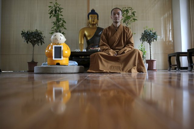 Master Xianfan sits next to robot Xian'er as he poses for photograph at Longquan Buddhist temple on the outskirts of Beijing, April 20, 2016. (Photo by Kim Kyung-Hoon/Reuters)