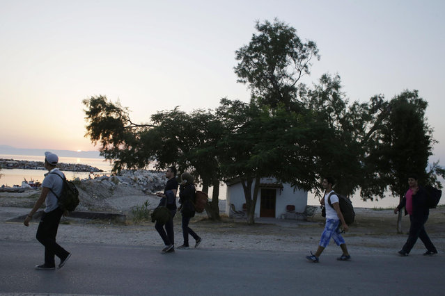 Syrian migrants walk next to a small Greek Orthodox church as the sun rises after their arrival from Turkish coasts at a beach in Mytilene, on the northeastern Greek island of Lesvos, early Tuesday, June 16, 2015. Lesvos has been bearing the brunt of a huge influx of migrants from the Middle East, Asia and Africa crossing from the Turkish coast to nearby Greek islands. More than 50,000 migrants have arrived in Greece already this year, compared to 6,500 in the first five months of last year. (AP Photo/Thanassis Stavrakis)