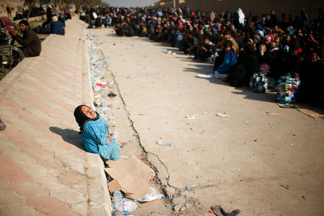 A displaced Iraqi woman reacts as she waits in a street for a truck to carry her to a safe place, as Iraqi forces battle with Islamic State militants, in western Mosul, Iraq March 8, 2017. (Photo by Suhaib Salem/Reuters)