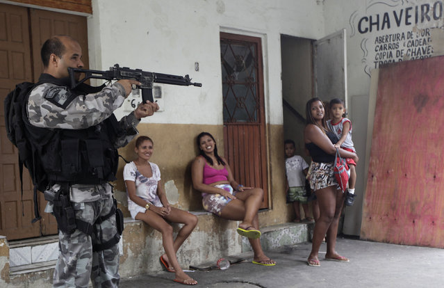 Residents observe a police officer take up position during an operation at the Mare slums complex in Rio de Janeiro March 25, 2014. (Photo by Ricardo Moraes/Reuters)