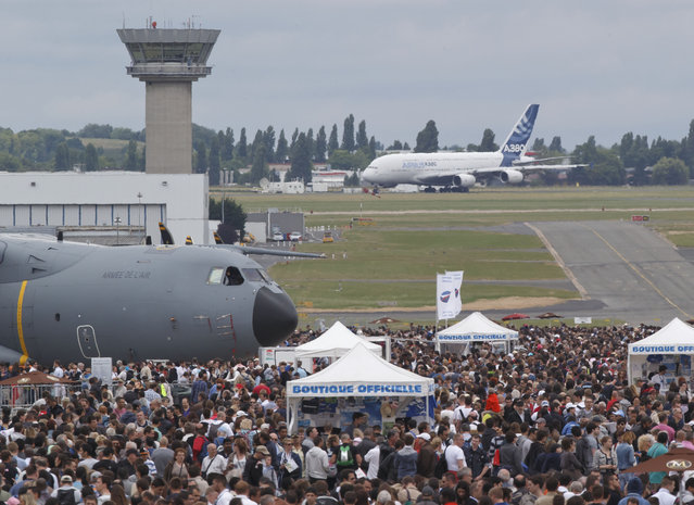 Visitors crowed the tarmac while an Airbus 380 is on takeoff roll for a demonstration flight during the closing day of the Paris Air Show in Le Bourget, north of Paris, Sunday,  June 21, 2015. Some 300,000 aviation professionals and spectators are expected at this week's Paris Air Show, coming from around the world to make business deals and see dramatic displays of aeronautic prowess and the latest air and space technology. (AP Photo/Michel Euler)